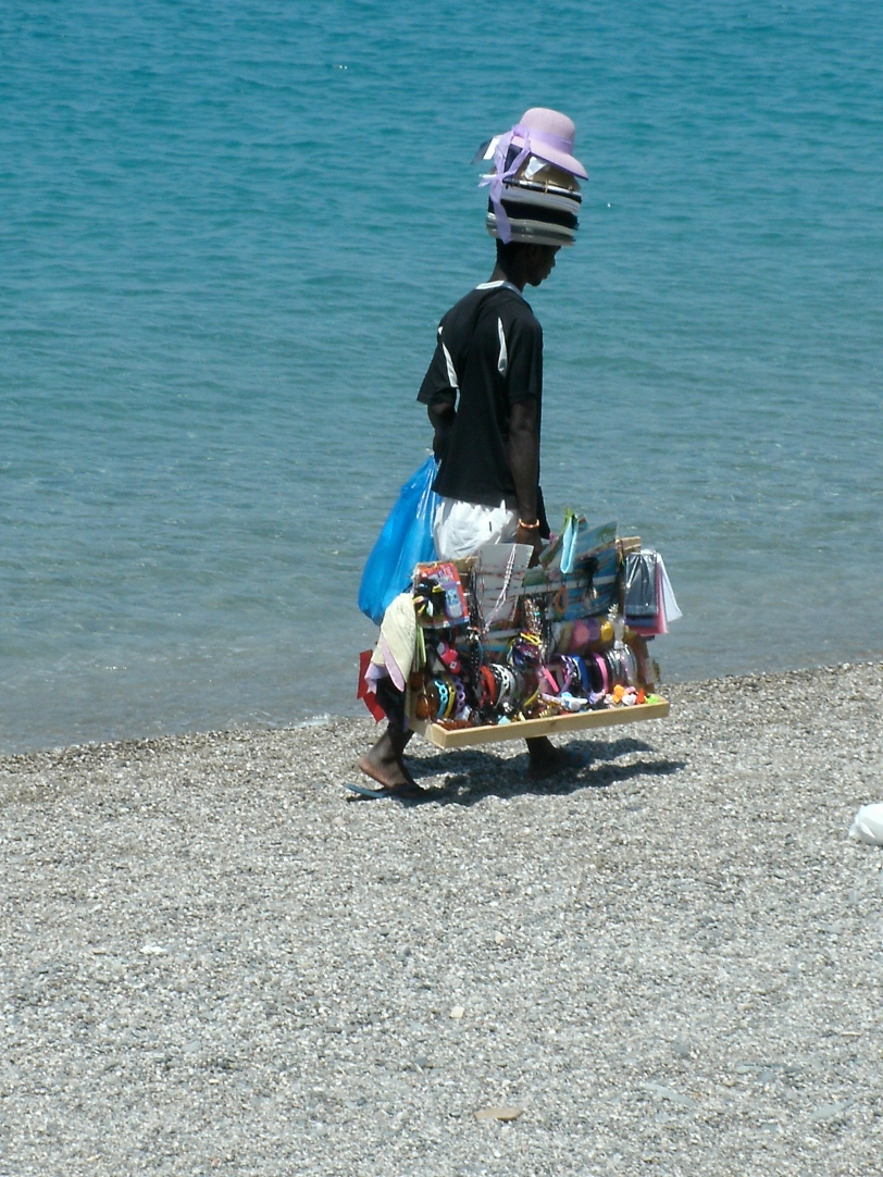 Immigrants who sell trinkets on the beaches spend hours walking up and down selling their wares for a pittance.